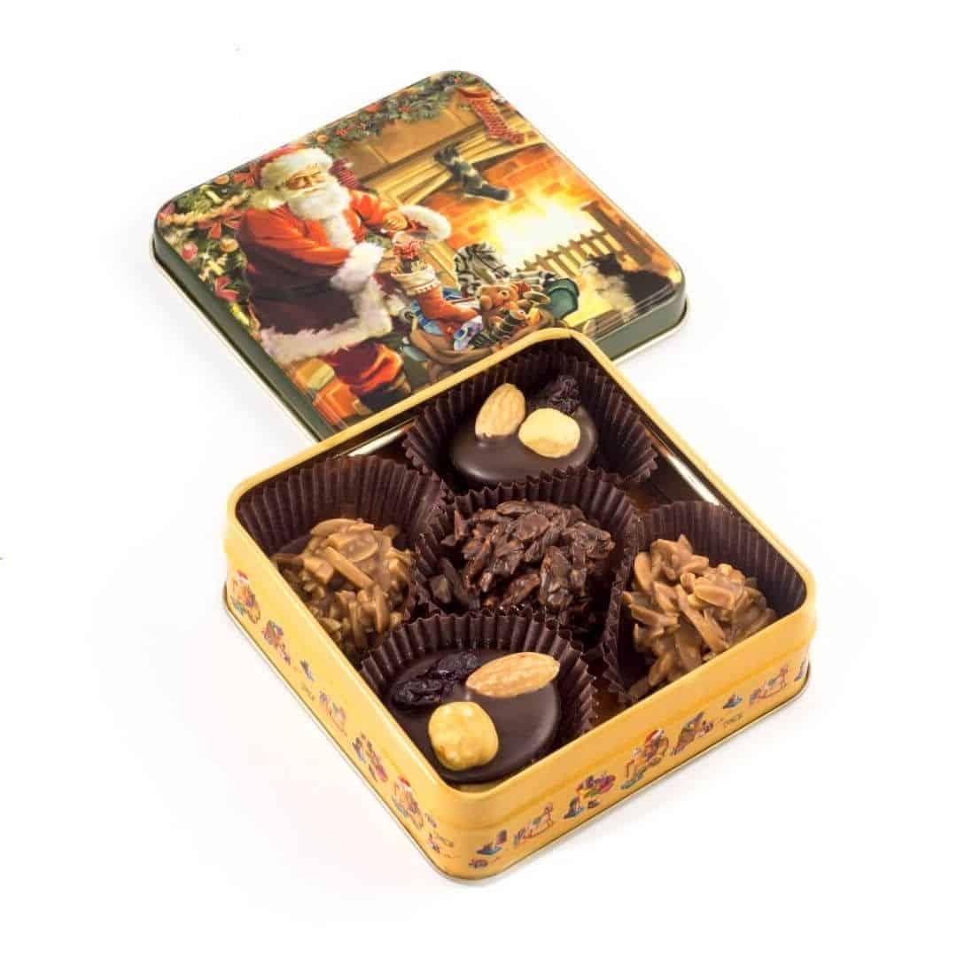 """Puszka """"Mikołaj"""" Świąteczna puszka wypełniona czekoladkami deserowymi z migdałami, orzechami laskowymi oraz migdałami w mlecznej czekoladzie."""