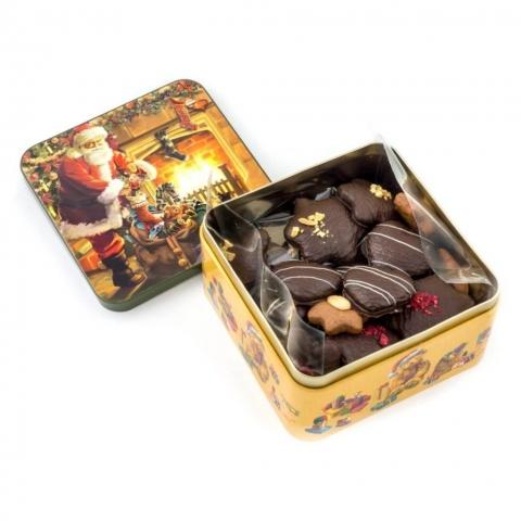 """Puszka """"Mikołaj"""" Puszka z dekorowanymi piernikami w czekoladzie deserowej z malinami, migdałami i białą czekoladą. Waga netto: 300 g wymiary: 150 x 150 mm"""