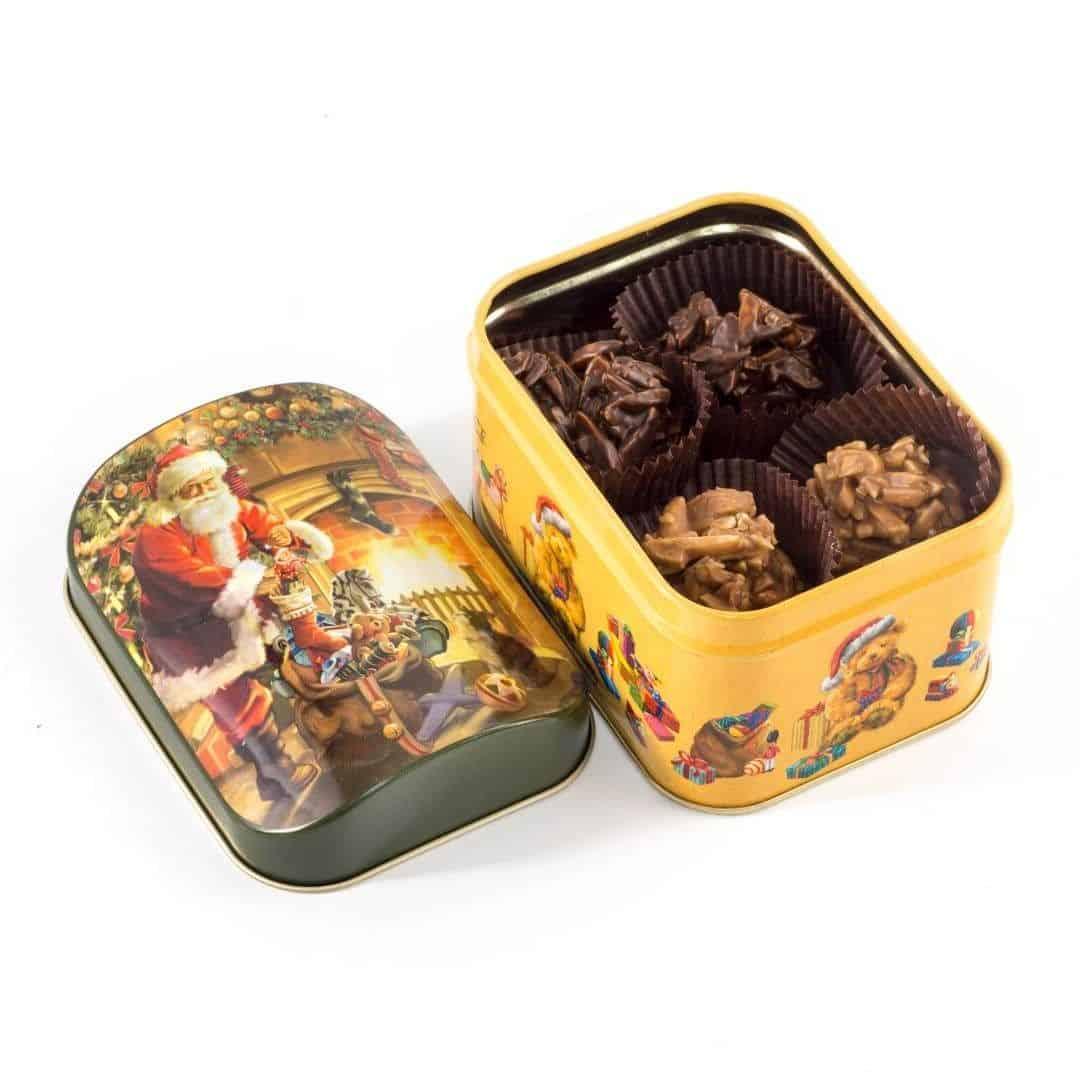 Świąteczna puszka wypełniona pralinami z migdałami czekoladzie mlecznej i deserowej.
